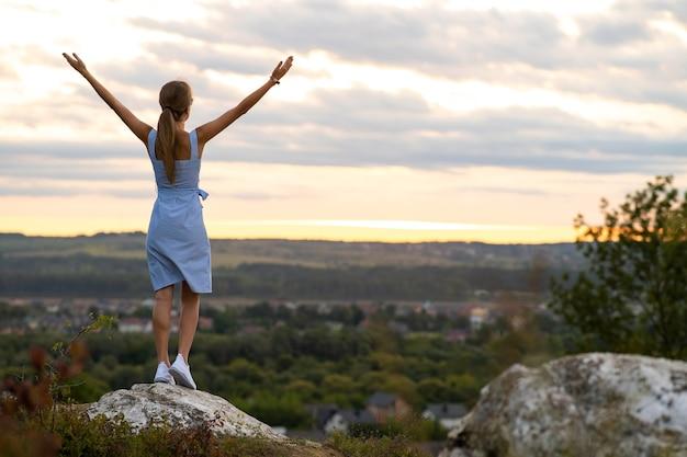 Una giovane donna in abito estivo alzando le mani in piedi all'aperto godendo della vista del tramonto giallo brillante.
