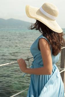 Giovane donna in abito estivo in piedi sul ponte e tenendo il cappello di paglia che guarda al mare