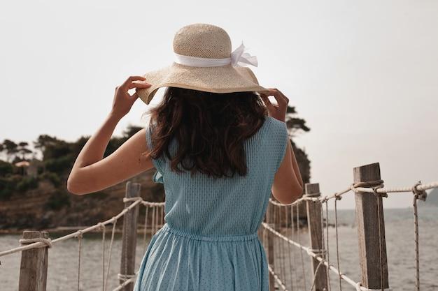 Giovane donna in abito estivo in piedi sul ponte e con cappello di paglia che guarda al mare
