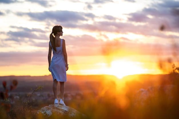 Una giovane donna in abito estivo in piedi all'aperto godendo della vista del tramonto giallo brillante.
