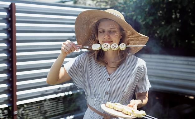 Giovane donna in cappello estivo e vestito che griglia carne e verdure all'aperto nel cortile. giovane donna in cappello estivo che odora di verdure grigliate all'aperto