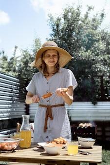 Giovane donna in cappello estivo e vestito che griglia carne e verdure all'aperto nel cortile. Foto Premium