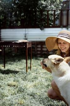 Giovane donna in cappello estivo che griglia carne all'aperto nel cortile sul retro, seduta con il suo cane, che fa uno spuntino all'animale domestico
