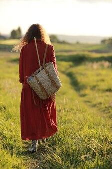 La giovane donna in vestito rosso di estate con lo zaino di paglia sta camminando nel prato verde che gode del sole. ragazza allegra e bella con i capelli ricci in una calda giornata di sole. vista posteriore.