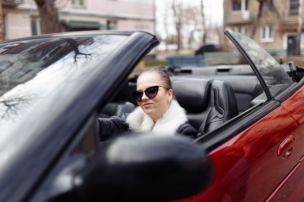 Giovane donna in occhiali da sole e una pelliccia in una costosa auto decappottabile