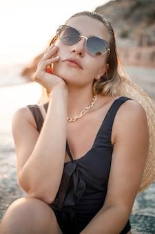 La giovane donna in occhiali da sole sta riposando al mare snella in un costume da bagno nero. messa a fuoco selettiva