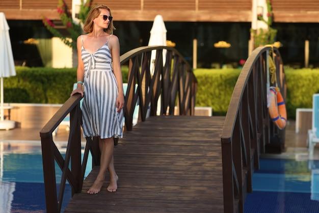 Giovane donna in occhiali da sole in piedi sul ponte di legno