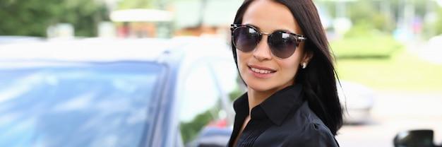 Giovane donna in occhiali da sole si trova vicino a un'auto nera in un parcheggio. prova su strada prima di acquistare un'auto. formazione alla guida
