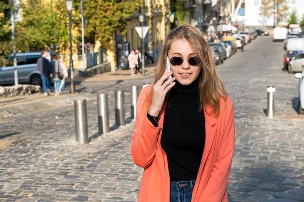 Giovane donna in occhiali da sole parlando al telefono cellulare