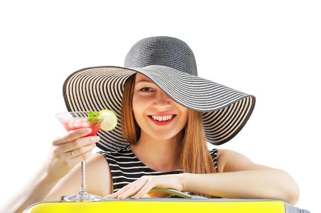 La giovane donna in cappello da sole beve cocktial