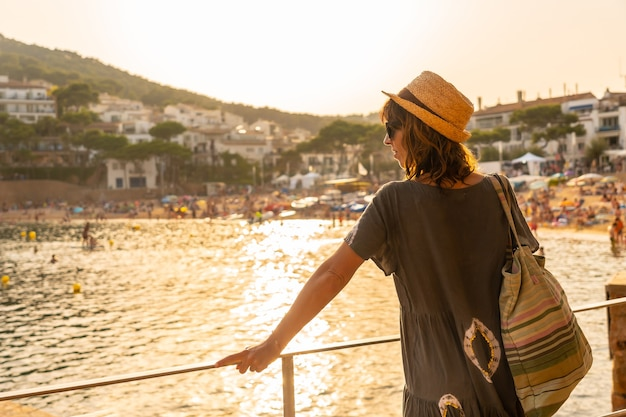 Una giovane donna al tramonto sulla costa di tamariu nella città di palafrugell. girona, costa brava nel mediterraneo