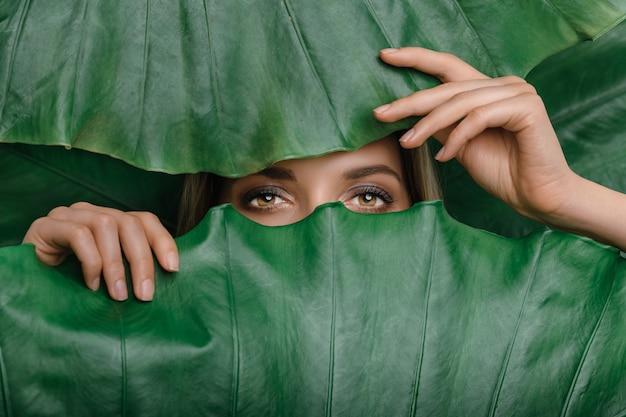 Giovane donna circondata da foglie tropicali