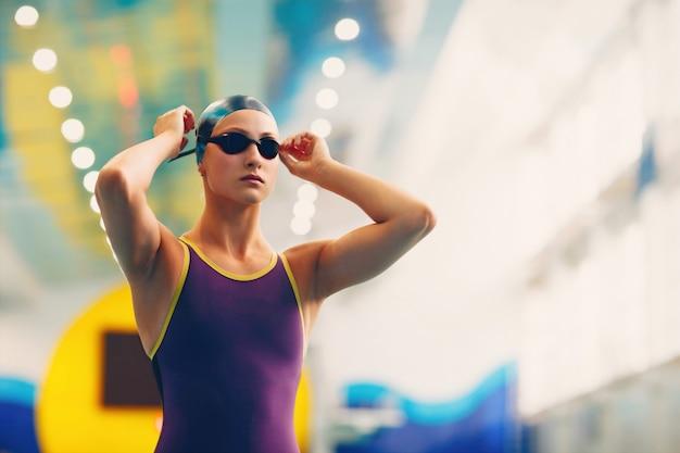 Nuotatore della giovane donna che indossa cappello e occhiali in piscina