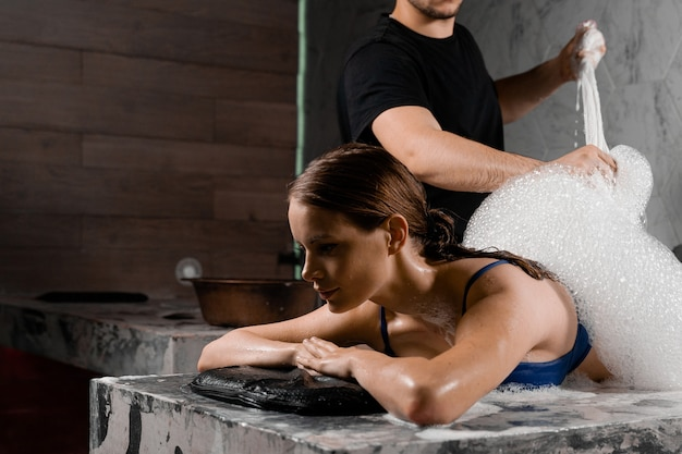 La giovane donna in costume da bagno sta posando sulla pietra nell'hammam turco. il massaggiatore fa il peeling con la schiuma per una ragazza attraente nella spa.