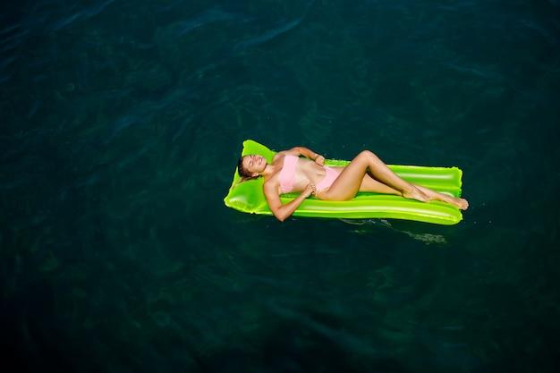Una giovane donna in costume da bagno nuota su un materasso gonfiabile luminoso in mare. concetto di vacanza estiva.