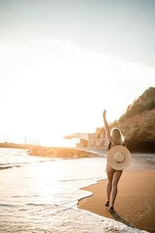 Giovane donna in costume da bagno con una bella figura in riva al mare al tramonto. messa a fuoco selettiva