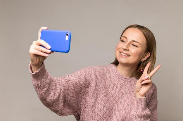 La giovane donna prende la foto del selfie sullo smartphone che mostra il sorriso del segno di pace v alla macchina fotografica sopra la parete dello studio