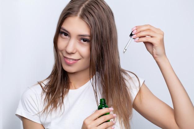 La giovane donna si prende cura dei suoi capelli usando oli naturali e balsami per la cura dei capelli.