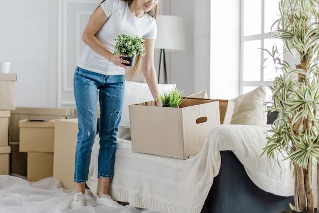 La giovane donna prende le sue piante preferite da una scatola di cartone. trasferirsi in un nuovo appartamento