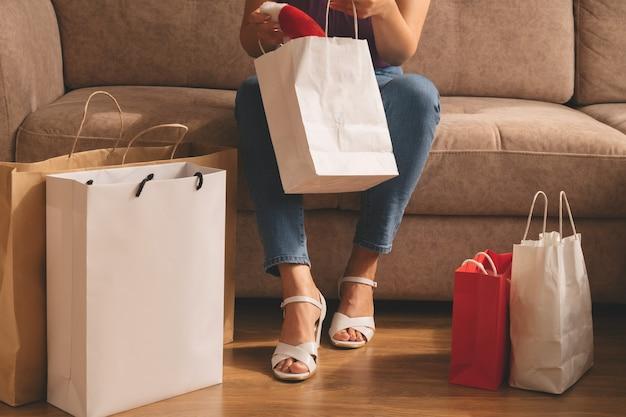 Una giovane donna tira fuori i suoi acquisti da una borsa mentre è seduta sul divano