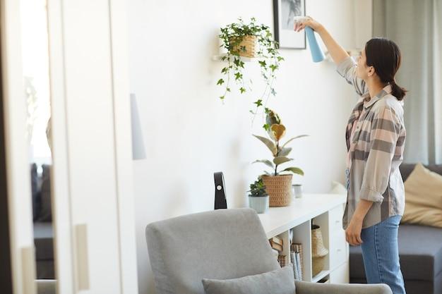Giovane donna che si prende cura dei suoi fiori nella stanza che spruzza acqua dalla bottiglia su di loro