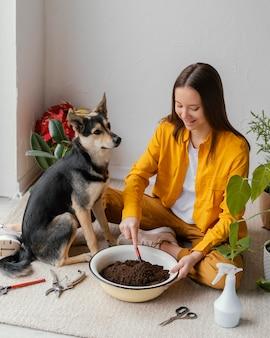 Giovane donna che si prende cura delle sue piante a casa