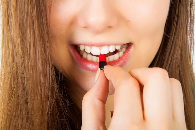 Giovane donna che cattura pillola rosso scuro