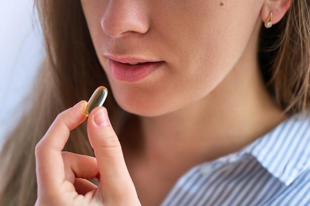 Giovane donna che prende integratore alimentare vitamina omega 3 per la salute. softgel di olio di pesce, vitamina d e vitamina c per sostenere l'immunità e la prevenzione delle malattie