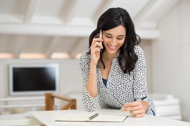 Giovane donna che prende appunti mentre parla al telefono