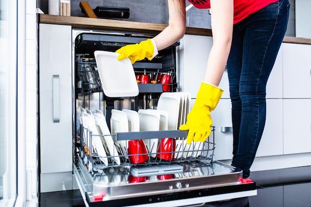Giovane donna che tira fuori i piatti puliti dalla lavastoviglie.