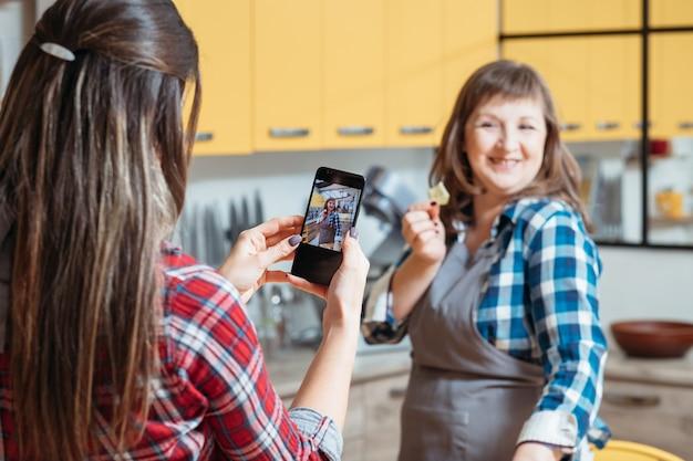 Giovane donna che cattura foto di un'altra signora in cucina durante la cottura