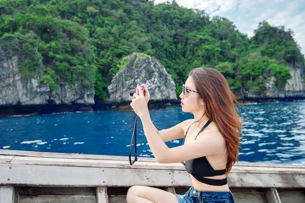 Giovane donna che cattura foto del bellissimo mare sulla fotocamera.