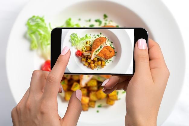 Una giovane donna che fotografa il cibo sullo smartphone, fotografando il pasto con la fotocamera mobile. realizzato per i social network. telefono cellulare con vista dall'alto
