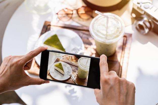 Giovane donna che cattura foto di cibo con lo smartphone nel ristorante