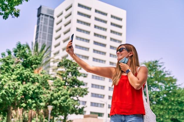 Giovane donna che scatta una foto con il suo telefono cellulare e la sua maschera.