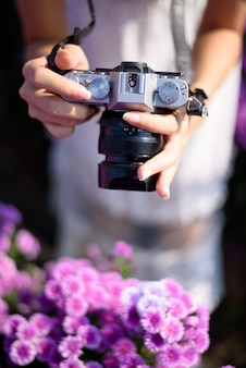 Giovane donna che cattura foto con la fotocamera in stile retrò