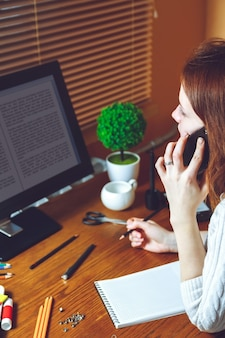 Giovane donna che parla al telefono mentre è seduto sul posto di lavoro