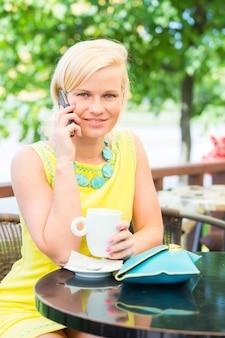 Giovane donna che comunica sul cellulare al cafe