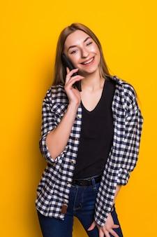 Giovane donna che parla al telefono contro il muro giallo