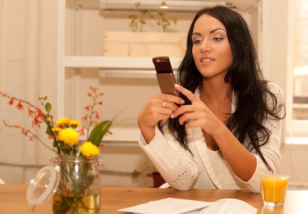Giovane donna che parla al telefono nel suo soggiorno
