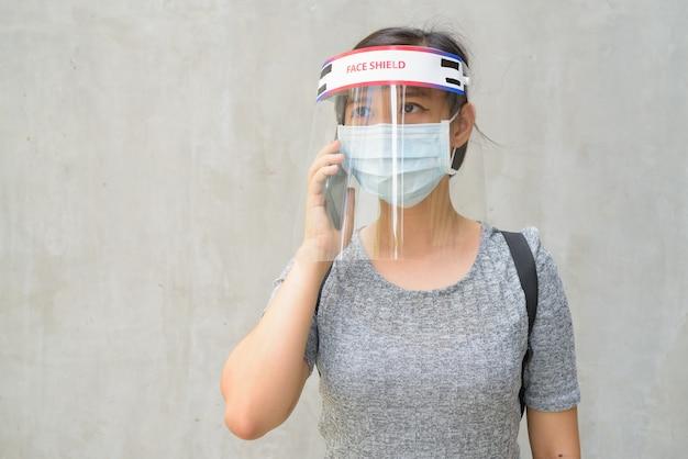 Giovane donna che parla al telefono con maschera e schermo facciale per la protezione dall'epidemia di virus corona all'aperto