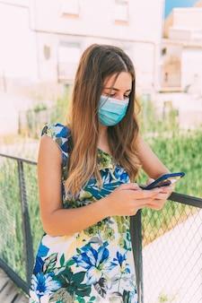 Giovane donna che parla al telefono con una mascherina medica sulla pandemia
