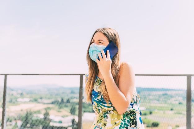 Giovane donna che parla al telefono con una mascherina medica