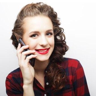Giovane donna che parla su smartphone su sfondo bianco
