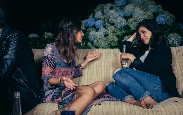 Giovane donna che parla con un'amica seduta sul divano in una festa all'aperto. concetto di amicizia e celebrazioni.