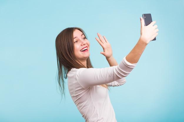 Giovane donna che parla con un amico tramite una videochiamata su uno smartphone. bella ragazza che ha un video