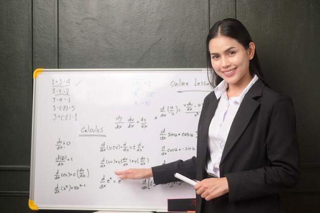 Un'insegnante di giovane donna sta utilizzando una telecamera per registrare lezioni online durante la quarantena, l'istruzione online, il concetto di apprendimento a distanza.