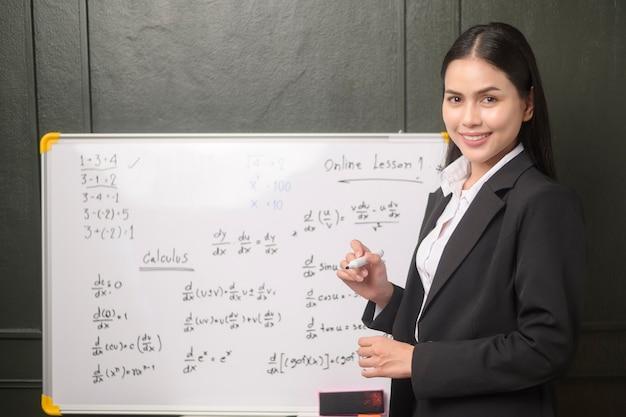 Un'insegnante di giovane donna sta utilizzando una telecamera per registrare lezioni online durante la quarantena, l'istruzione online, il concetto di apprendimento a distanza