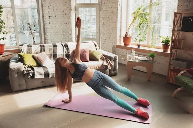 Giovane donna che insegna a casa corsi online di fitness, aerobica, stile di vita sportivo mentre è in quarantena. diventare attivi mentre si è isolati, benessere, concetto di movimento. allenamento della parte inferiore del corpo, cardio.
