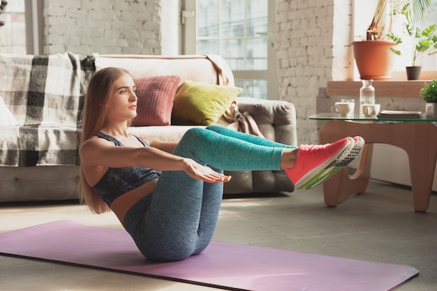 Giovane donna che insegna a casa corsi online di fitness, aerobica, stile di vita sportivo mentre è in quarantena.